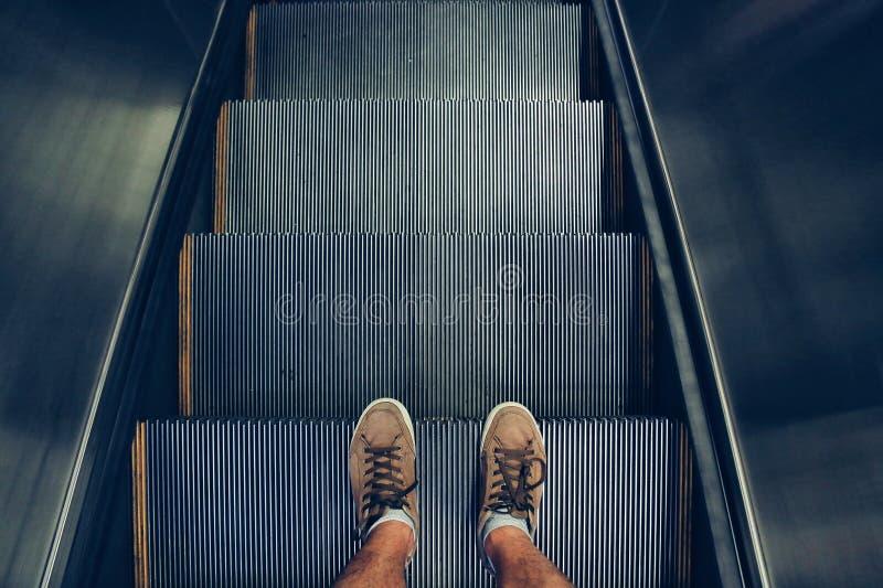 Selfie de pies en zapatos de la zapatilla de deporte en pasos de escalera móvil en estilo del vintage imagen de archivo