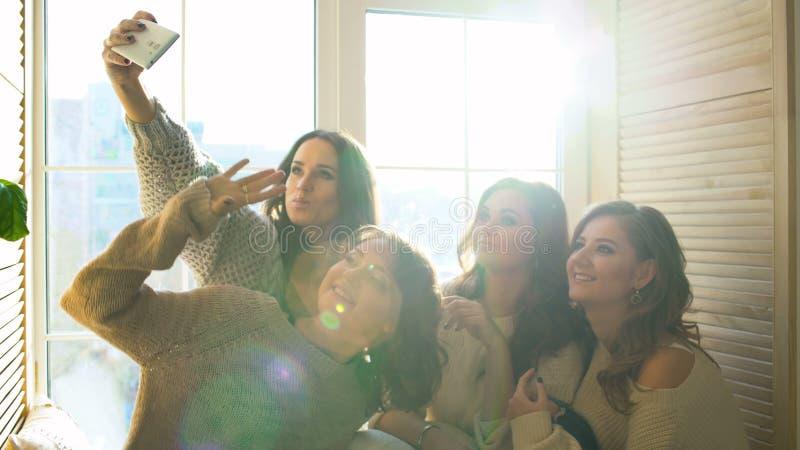 Selfie de pousse de quatre beau filles se reposant sur la fenêtre Amies ayant l'amusement et le rire dans la chambre à coucher banque de vidéos