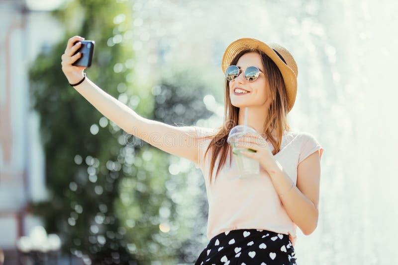 Selfie de prise de fille de Youngpretty des mains avec le téléphone sur la rue de ville d'été Concept de la vie urbaine photo stock
