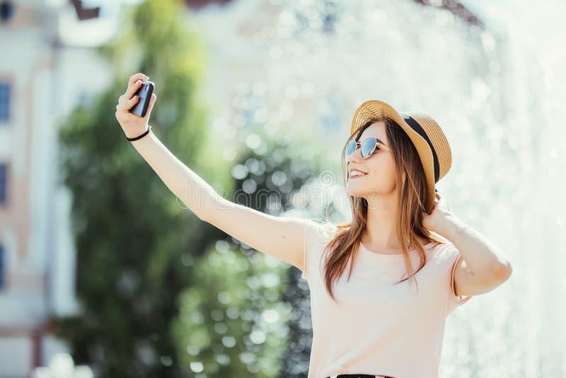 Selfie de prise de fille de Youngpretty des mains avec le téléphone sur la rue de ville d'été Concept de la vie urbaine photo libre de droits