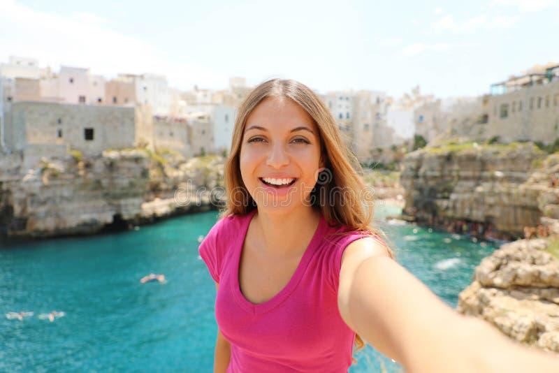 Selfie de sorriso da tomada da mulher em suas férias de verão em Polignano uma égua, mar Mediterrâneo, Itália imagens de stock