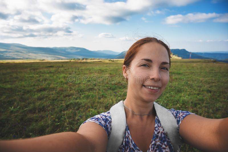 Selfie de sourire de prises de jeune femme sur le fond de montagne, voyage d'été photographie stock