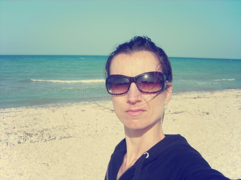 Selfie de una mujer joven en la playa; estilo descolorado, retro imagen de archivo