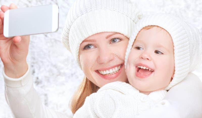Selfie in de winter gelukkige familiemoeder met dochter en gefotografeerde zelf op mobiele telefoon royalty-vrije stock foto