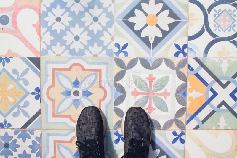 Selfie dei piedi con le scarpe della scarpa da tennis sulle mattonelle d'annata del modello di arte, vista superiore fotografia stock libera da diritti