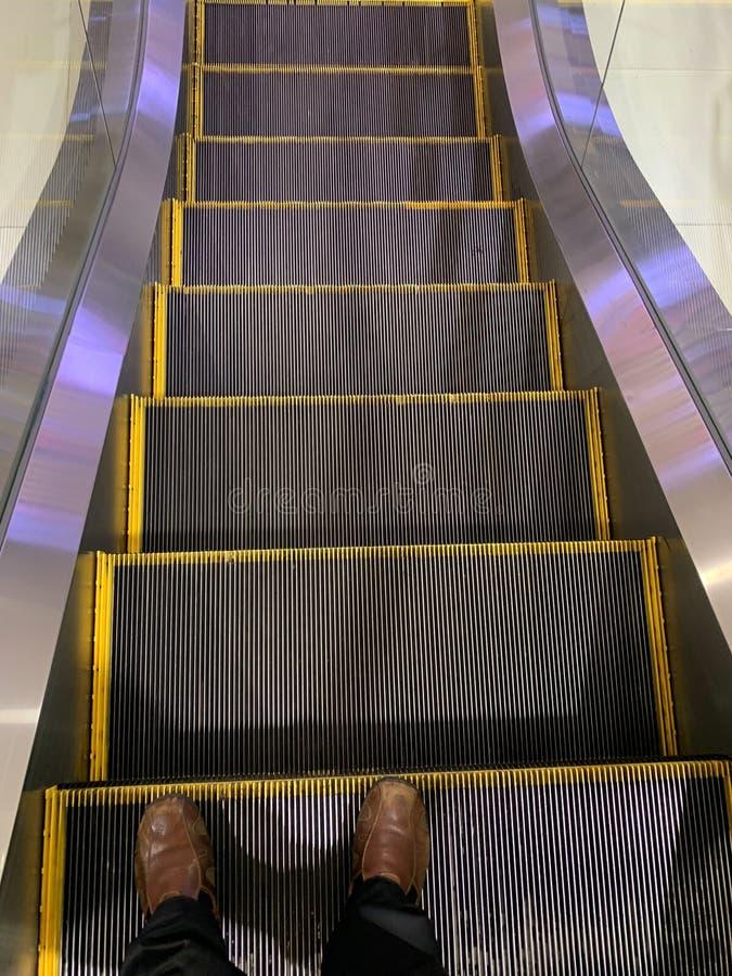 Selfie dei piedi dell'uomo in scarpe marroni sui gradini di scala mobile nell'aeroporto immagine stock