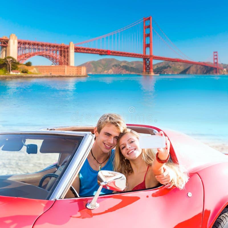 Selfie del Golden Gate convertible del coche de los pares jovenes foto de archivo