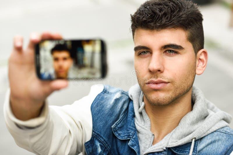 Selfie del hombre joven en fondo urbano con un smartphone imágenes de archivo libres de regalías