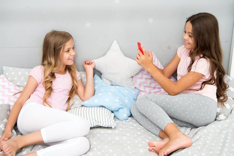 Selfie del modelado de los niños - dos niñas que hacen el selfie en smartphone niños de las niñas que modelan en dormitorio foto de archivo