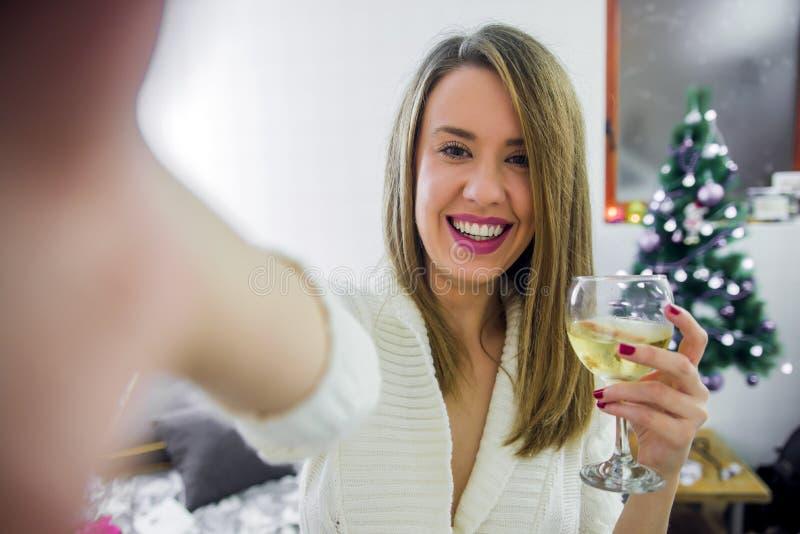 Selfie della presa della donna sul telefono con il vetro della tenuta dell'albero di Natale della vite, celebrante nuovo anno Con fotografia stock