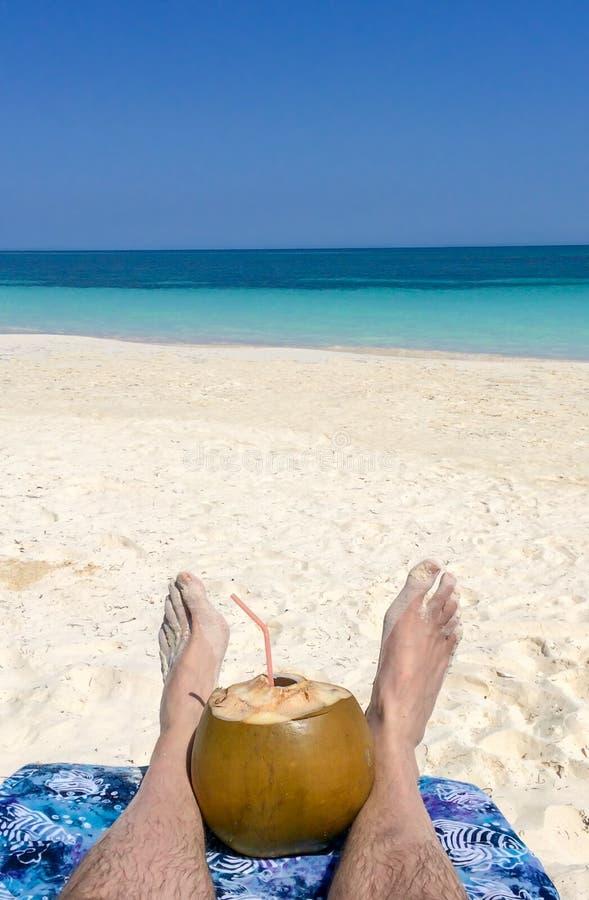 Selfie des pieds et du jus frais de noix de coco, plage tropicale image stock