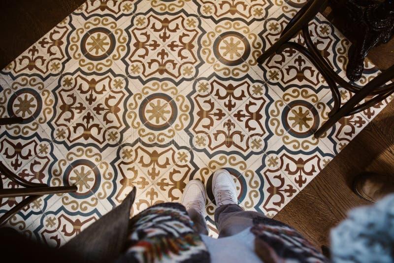 Selfie dos pés com as sapatas da sapatilha na parte superior do assoalho de telhas do teste padrão da arte foto de stock