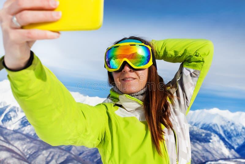 Selfie för skidåkarekvinnatagande med telefonen över berg arkivfoton