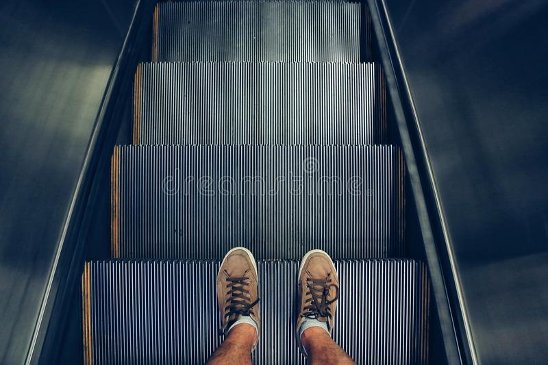 Selfie of feet in sneaker shoes on escalator steps in vintage style stock image