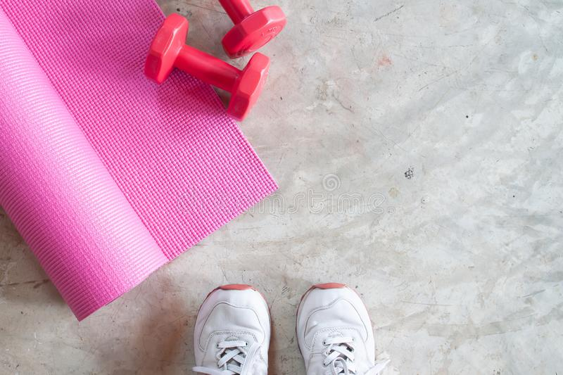 Selfie of feet sporty girl with yoga mat and dumbbells on concrete floor. Fitness and workout, Healthy. Concept royalty free stock image