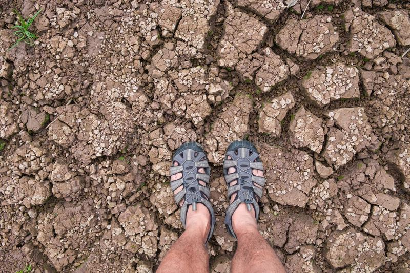 Selfie of feet Traveler men with hiking sandals standing on On the ground that separates the cracked. royalty free stock image