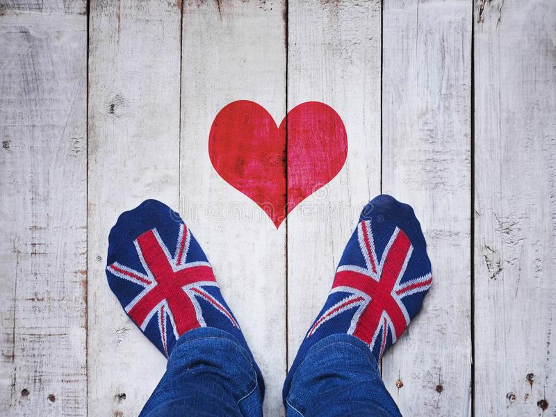Selfie feet wearing socks with British flag pattern. On white wooden grunge floor background royalty free stock photos