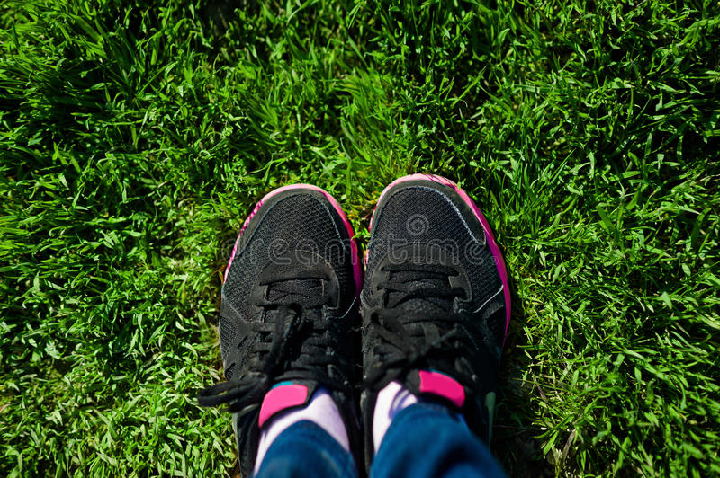 Selfie of female feet on black sneakers standing on green grass stock photos