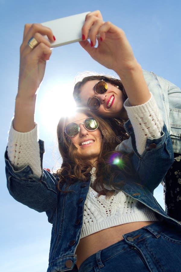Selfie flickor som tar foto med en smartphone royaltyfri fotografi