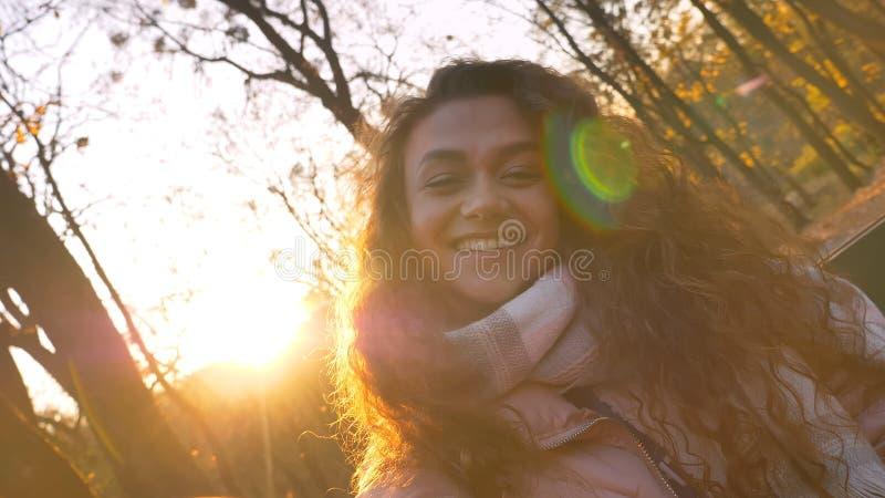 Selfie-foto da menina caucasiano encaracolado-de cabelo bonito com a cabeça inclinado que olha felizmente na câmera no parque out imagem de stock royalty free