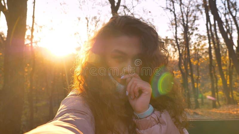 Selfie-foto da menina caucasiano encaracolado-de cabelo bonito com os dedos sob o nariz que olha na câmera no parque outonal enso foto de stock royalty free