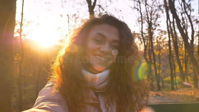 Selfie-foto da menina caucasiano encaracolado-de cabelo bonito que olha felizmente na câmera no parque outonal ensolarado fotos de stock royalty free