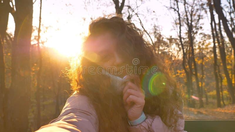 Selfie-foto da menina caucasiano encaracolado-de cabelo bonito que toca em seu colar e que olha na câmera no parque outonal ensol foto de stock