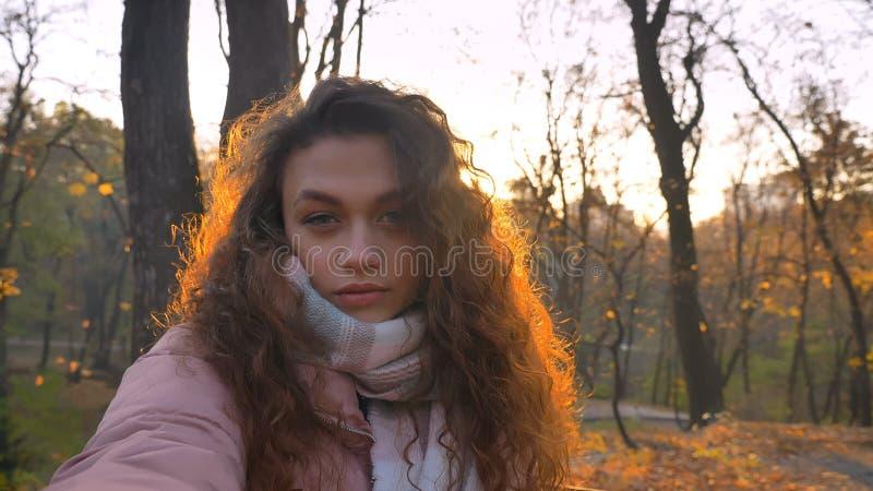 Selfie-foto da menina caucasiano encaracolado-de cabelo que olha seriamente na câmera no parque outonal ensolarado fotografia de stock