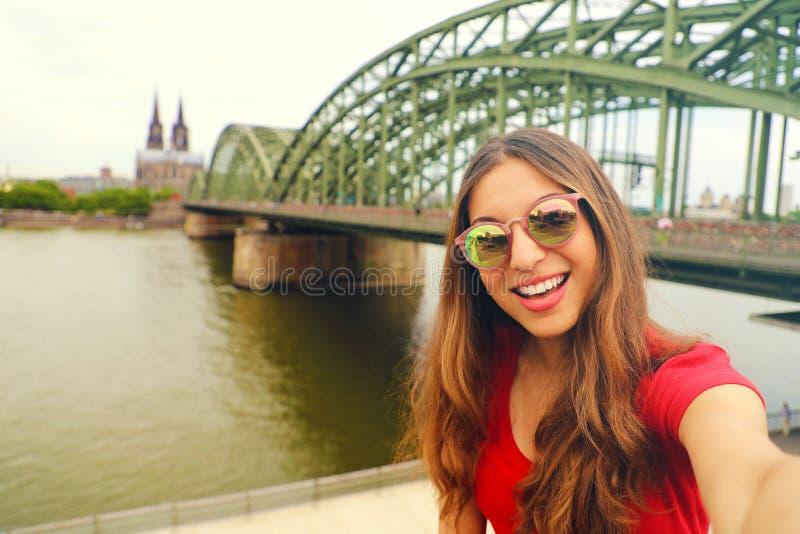 Selfie-Foto der jungen Modefrau in Köln mit Hohenzollern-Brücke und Kathedrale auf dem Hintergrund, Köln, Deutschland stockfotos
