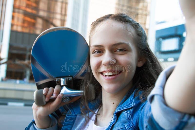 Selfie-Foto des lächelnden Studentenmädchens, das ein Skateboard auf ihrer Schulter hält lizenzfreie stockfotos
