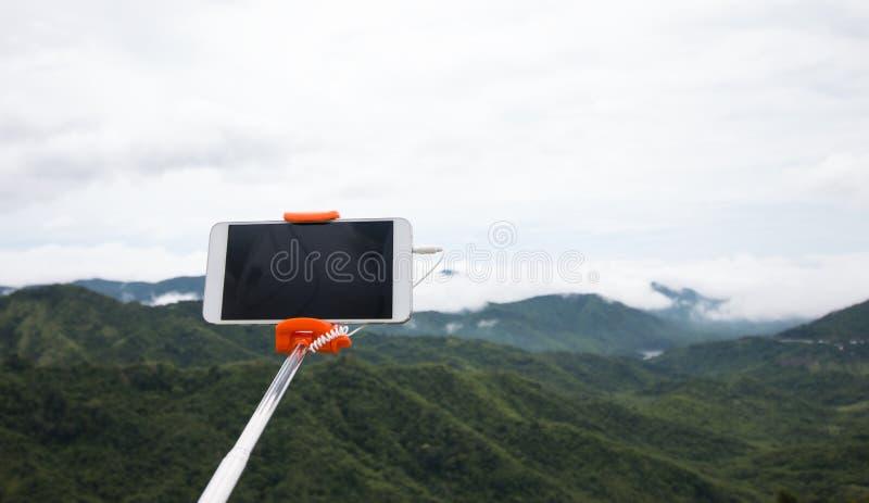 Selfie fotobegrepp: Åtlöje upp den Extensible selfiepinnen eller monopod med mobiltelefonen som tar bilden som skjutas på den uto royaltyfri foto