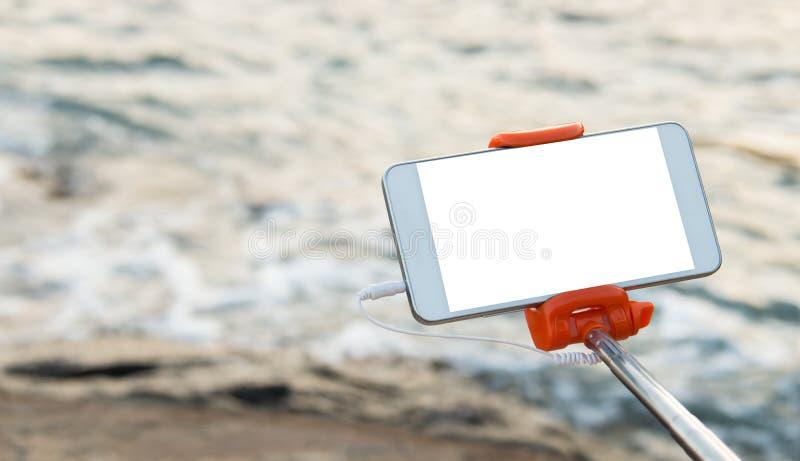 Selfie fotobegrepp: Åtlöje upp den Extensible selfiepinnen eller monopod med mobiltelefonen som tar bilden som skjutas på den uto arkivbild