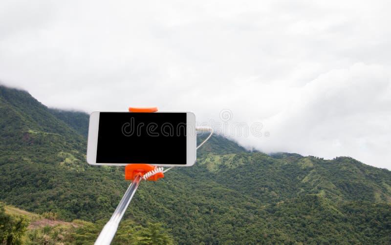 Selfie fotobegrepp: Extensible selfiepinne eller monopod med mobiltelefonen som tar bilden som skjutas på den utomhus- bergsikten fotografering för bildbyråer