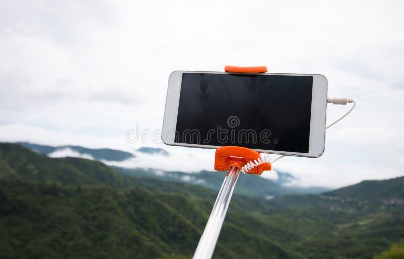 Selfie fotobegrepp: ?tl?je upp den Extensible selfiepinnen eller monopod med mobiltelefonen som tar bilden som skjutas p? den uto royaltyfri bild