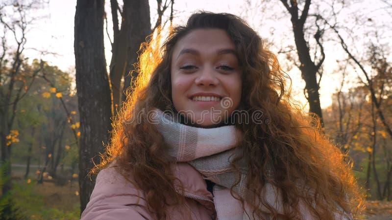 Selfie-fotoet av denhaired caucasian flickan som håller ögonen på med positiv munterhet in i kamera i soligt höstligt, parkerar arkivbilder