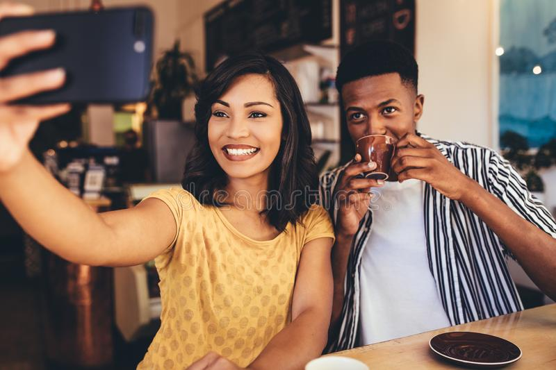 Selfie with friend at cafe. Young women taking selfie with her friend drinking coffee at a cafe. Young friends sitting together at coffee shop taking selfie royalty free stock images