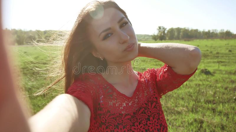 Selfie. The girl makes selfie, takes pictures of herself in nature. Girl hair breeze lifestyle stock photo