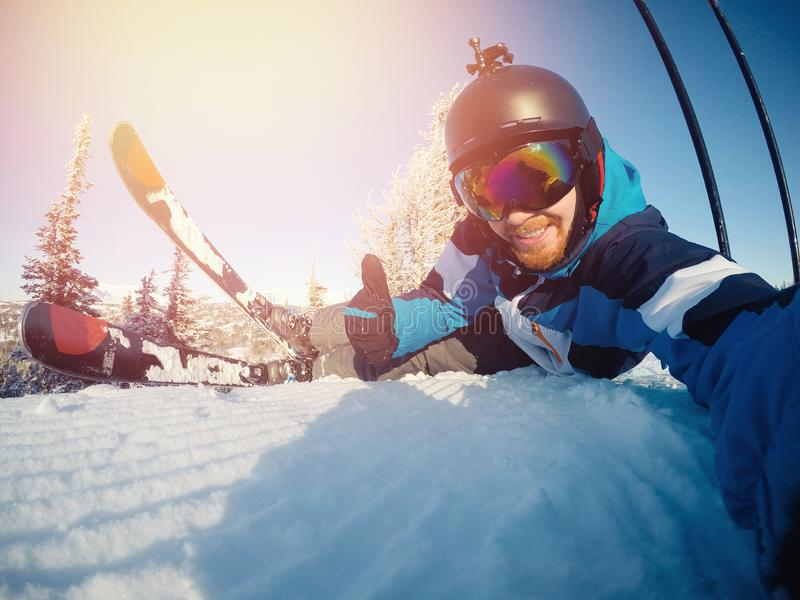 Selfie Guy sportsman goes on normal skiing on ski slope with action camera. Sunset. winter royalty free stock photography