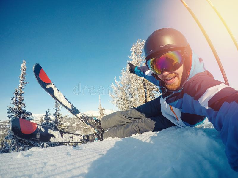 Selfie Guy sportsman goes on normal skiing on ski slope with action camera. Sunset. winter royalty free stock image