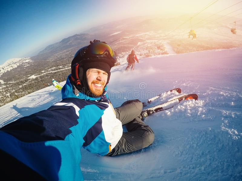 Selfie Guy sportsman goes on normal skiing on ski slope with action camera. Sunset. winter stock photography