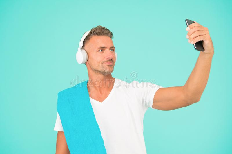 Selfie in gym concept. Sportsman smartphone and headphones. Healthy lifestyle. Gym aesthetics. Mature but still in good royalty free stock photography