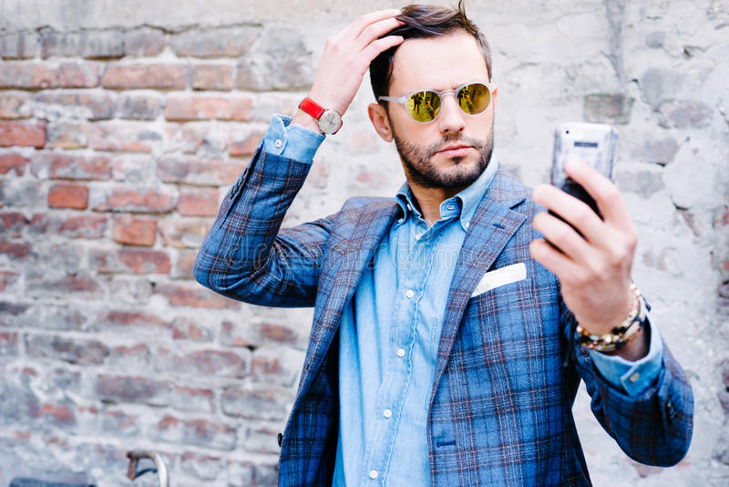 Selfie. Handsome man with glasses ina suit, against old vintage wall, outdoors. taking a selfie stock images
