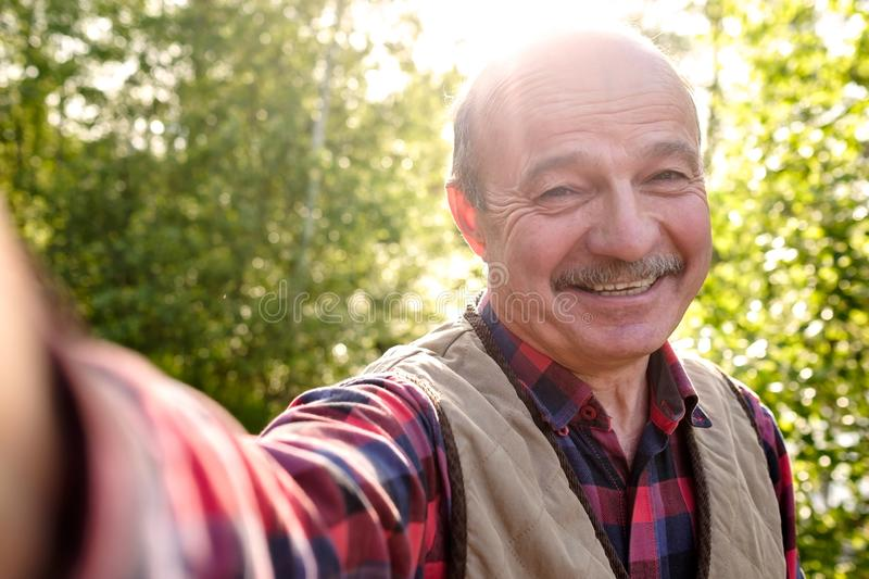Selfie from handsome senior hispanic man on sunny day. royalty free stock images