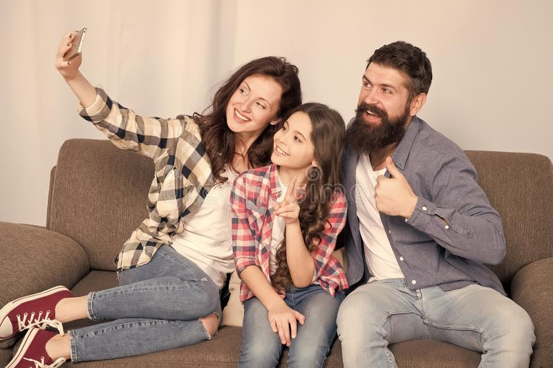 Selfie. Happy family at home. Modern smartphone. Little girl use smartphone with mother and father. bearded man and. Selfie. Happy family at home. Modern stock image