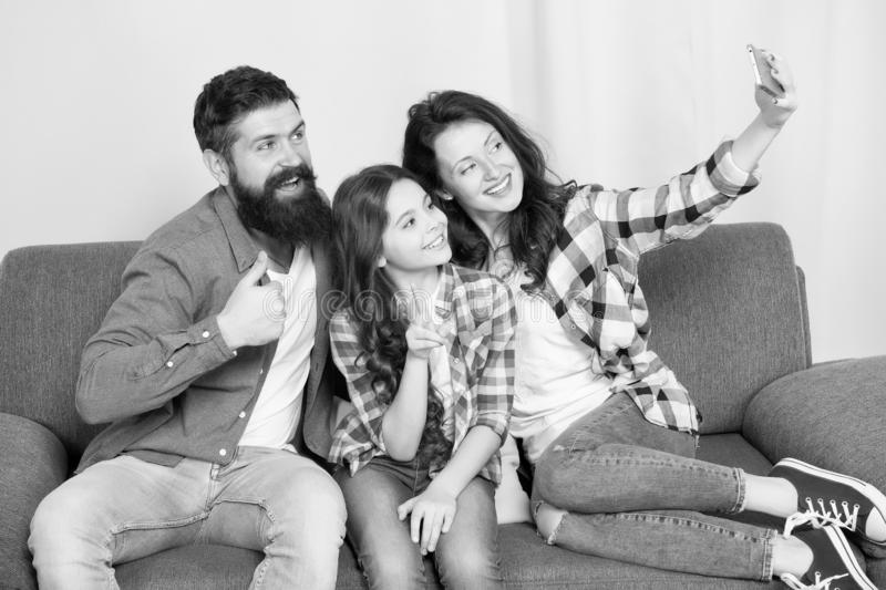 Selfie. Happy family at home. Modern smartphone. Little girl use smartphone with mother and father. bearded man and stock image