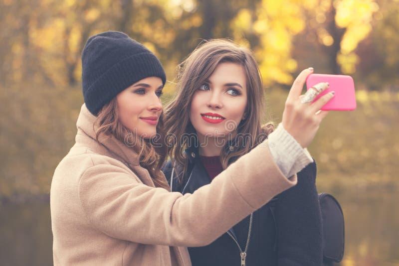 Selfie Lächelnde Modelle mit dem Handy, der Selfie nimmt lizenzfreie stockfotos