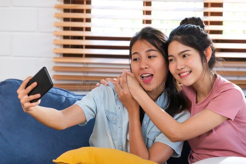 Selfie lésbica asiático feliz com telefone celular no sofá na casa Conceito do estilo de vida de LGBTQ imagem de stock
