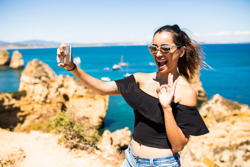 Selfie latino della presa della donna di bellezza dal telefono alla cima di bella scogliera s ed alle rocce dell'Oceano Atlantico fotografie stock