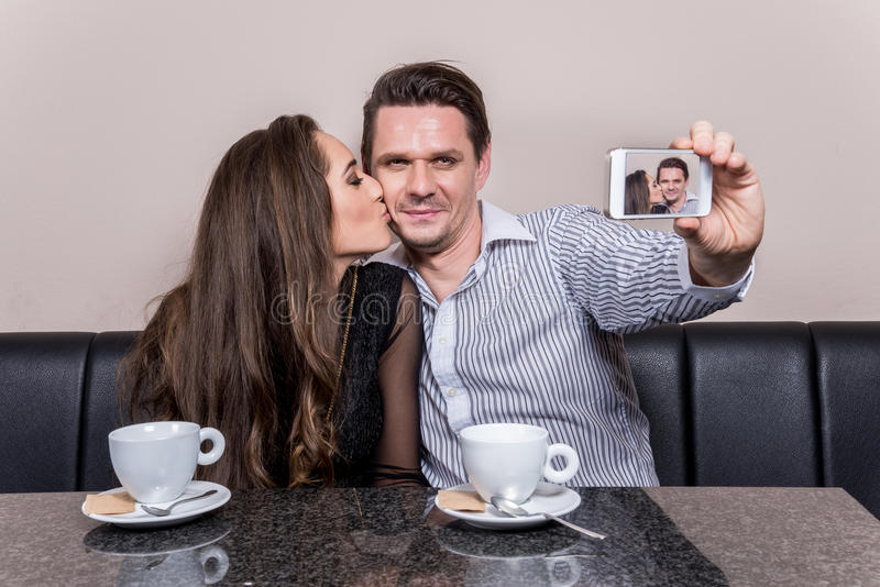 Selfie. Loving couple taking selfie at cafe royalty free stock photo