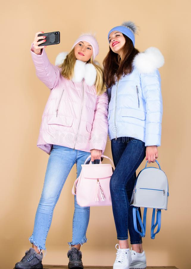 Selfie making. women in padded warm coat. xmas vacation. happy winter holidays. Students friendship. girls in beanie royalty free stock image